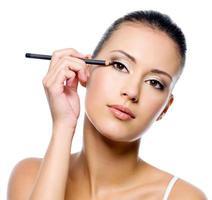 donna che applica eyeliner sulla palpebra con pensil foto