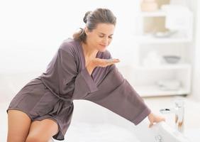 giovane donna felice sentente l'odore del sale da bagno foto