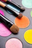pennelli per il trucco e palette di ombretti colorati su nero vicino foto