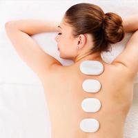 donna che si distende nel salone spa con terapia con pietre foto