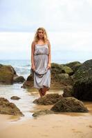 donna bionda che propone alla spiaggia foto