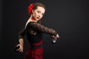 donna spagnola che balla flamenco sul nero foto