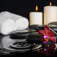 concetto di spa di pietre zen con gocce, orchidea viola foto
