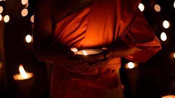 mani del monaco buddista che tengono la tazza di candela foto