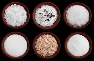 sei piatti in terracotta con sale marino diverso sul nero foto
