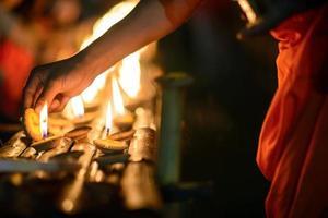 mani del monaco buddista che accendono candela foto