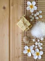 sapone, conchiglia, pietre e fiori di tiare sullo sfondo in legno foto