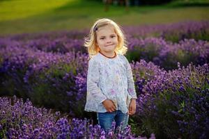 bambina carina in un campo di lavanda foto