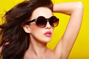 giovane donna caucasica splendida che indossa gli occhiali da sole foto