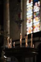 candele della chiesa con vetrate sullo sfondo