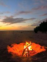 fuoco sulla spiaggia al tramonto nel tuamotus, sud pacifico.
