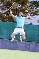 Ritratto di giovane esclamando maschio caucasico giocatore di tennis foto