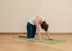 donna caucasica sta praticando yoga in studio (goasana) foto