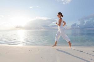 donna caucasica fare jogging in riva al mare foto
