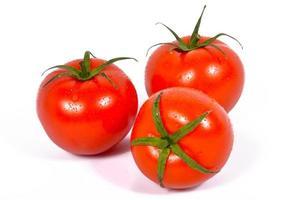tre pomodori freschi con foglie verdi foto