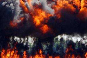 denso fumo nero che sale da un'esplosione fiammeggiante foto