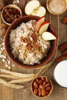 farina d'avena saporita con le noci e le mele sulla tavola di legno foto