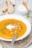 zuppa di carote con mandorle, yogurt e crescione in un piatto foto