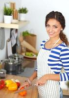 giovane donna che taglia le verdure in cucina foto