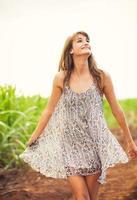 splendida ragazza che cammina nel campo, stile di vita estivo foto