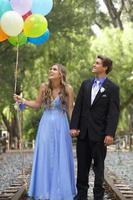 coppia di ballo adolescente felice che cammina sui binari del treno con palloncini