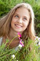 Ritratto di sorridente ragazza bionda sopra i fiori, verde