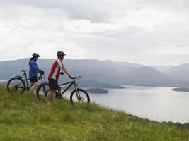 coppia con biciclette sul lago foto