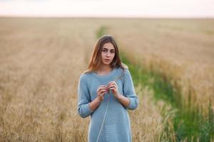 bella signora bruna nel campo di grano al tramonto