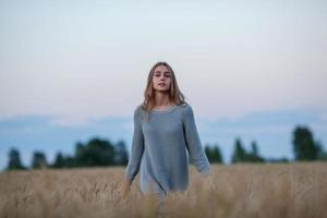 bella signora bruna nel campo di grano al tramonto foto