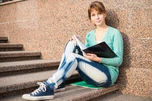 ragazza che si siede sulle scale e che legge nota foto