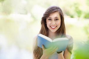 libro di lettura della giovane donna all'aperto foto