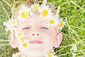 giovane ragazzo biondo con una corona di margherite foto