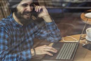 uomo giovane hipster lavorando sul portatile in caffetteria foto