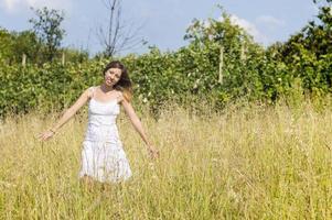 giovane donna nel campo che indossa un abito bianco
