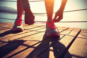donna di sport stile di vita sano legare i lacci delle scarpe foto