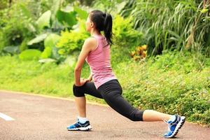 donna asiatica di stile di vita sano che allunga le gambe foto