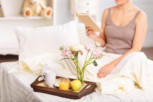 bella ragazza facendo colazione a letto foto