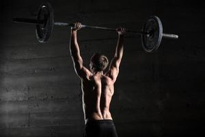ritratto di un atleta bello da dietro. atleta alza il foto