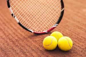 stretta di palline da tennis e racchetta foto