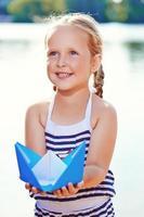 bambina sveglia che tiene la barca di origami all'aperto foto