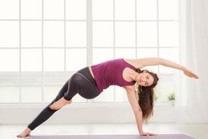 giovane donna che fa esercizi di yoga foto