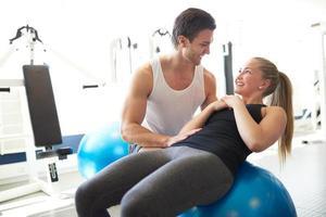 istruttore di forma fisica che assiste una donna sulla palla di esercizio foto