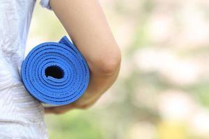 giovane donna che tiene una stuoia di yoga nel giardino di sakura