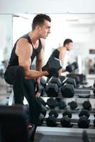 uomo che fa esercizi con manubri muscoli bicipiti foto