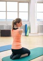 donna che fa esercizi di stretching in palestra foto