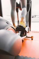 colpo del primo piano delle gambe di una femmina utilizzando trainer ellittico foto
