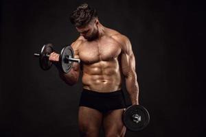 ragazzo muscoloso bodybuilder che fa le esercitazioni con i dumbbells foto