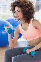 giovane donna che si esercita con i dumbbells in ginnastica foto