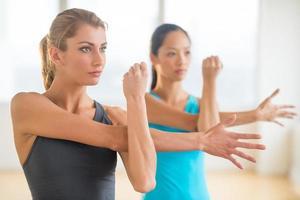 donne che distolgono lo sguardo mentre fanno esercizio di stretching