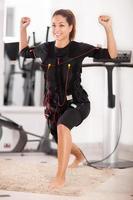 esercizio della giovane donna sulla macchina di elettro stimolazione foto